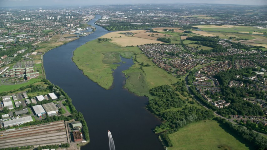 6K stock footage aerial video fly over River Clyde toward farm fields and residential communities, Glasgow, Scotland Aerial Stock Footage | AX110_146