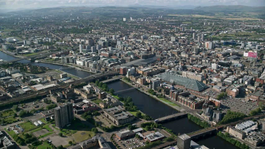 6K stock footage aerial video of River Clyde with bridges by city buildings, Glasgow, Scotland Aerial Stock Footage | AX110_167
