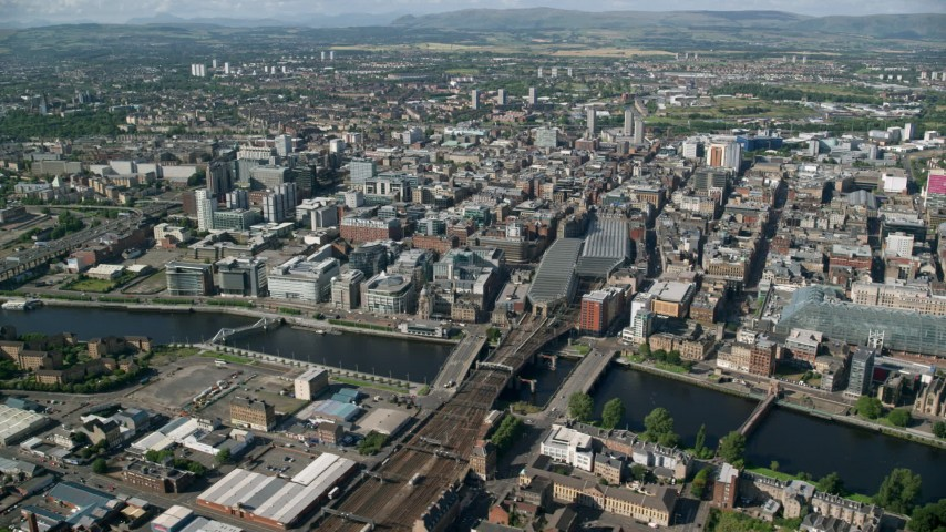 6K stock footage aerial video of River Clyde bridges, Glasgow Central Station, and city buildings, Glasgow, Scotland Aerial Stock Footage | AX110_168