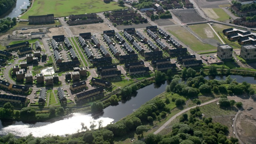 6K stock footage aerial video of riverfront row houses along River Clyde, Glasgow, Scotland Aerial Stock Footage | AX110_189