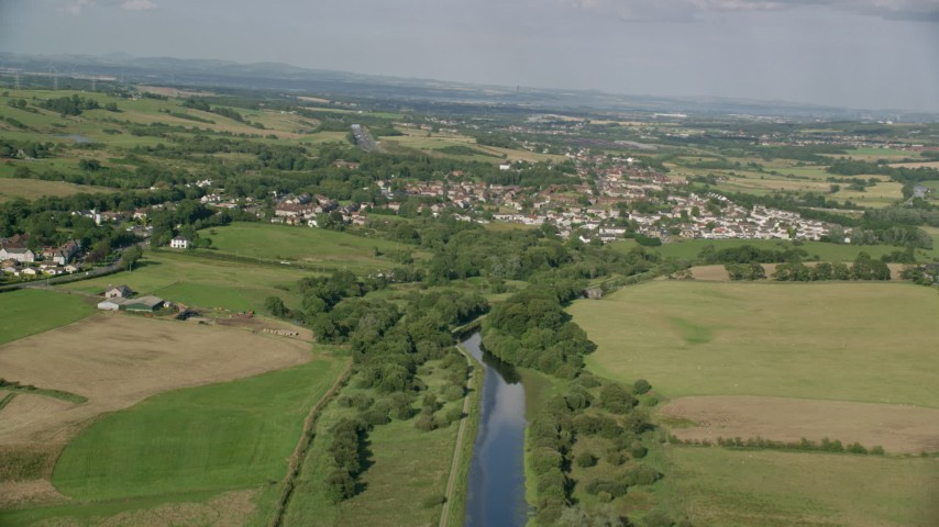 6K stock footage aerial video of a river and green farm fields around a rural village, Bonnybridge, Scotland Aerial Stock Footage | AX111_002