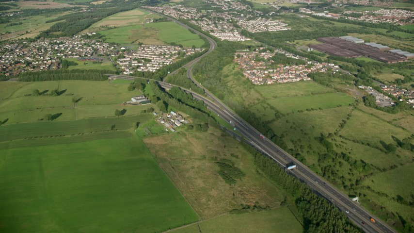 6K stock footage aerial video approach M80 Highway through farmland and a village, Bonnybridge, Scotland Aerial Stock Footage | AX111_003