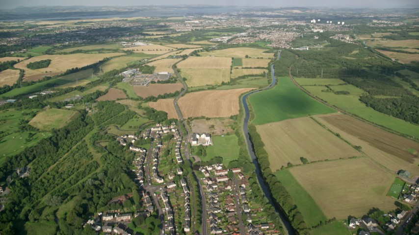 6K stock footage aerial video fly over village homes and farm fields by a river, Bonnybridge, Scotland Aerial Stock Footage | AX111_005