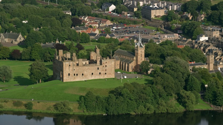 6K stock footage aerial video of historic Linlithgow Palace and St. Michael's Parish Church, Scotland Aerial Stock Footage | AX111_011
