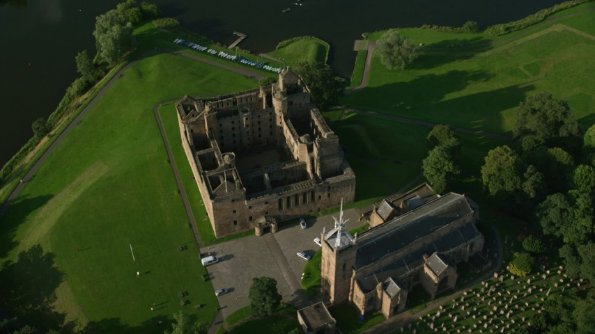 6K stock footage aerial video tilt to bird's eye of Linlithgow Palace and St. Michael's Parish Church, Scotland Aerial Stock Footage | AX111_023