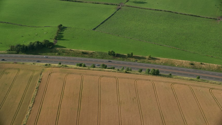 6K stock footage aerial video of tracking a black Car on M9 Highway through farmland, Linlithgow, Scotland Aerial Stock Footage | AX111_025