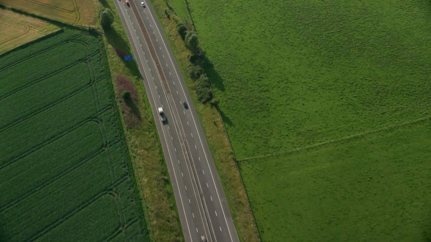6K stock footage aerial video of tracking a black car on M9 Highway through farmland, Linlithgow, Scotland Aerial Stock Footage | AX111_026