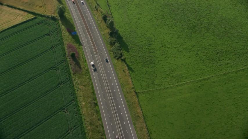 6K aerial video of tracking a black car on M9 Highway through farmland, Linlithgow, Scotland Aerial Stock Footage AX111_026