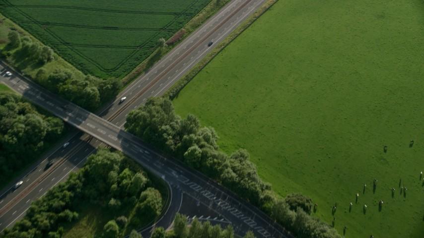 6K aerial video of a black car on M9 Highway through farmland, Linlithgow, Scotland Aerial Stock Footage | AX111_027