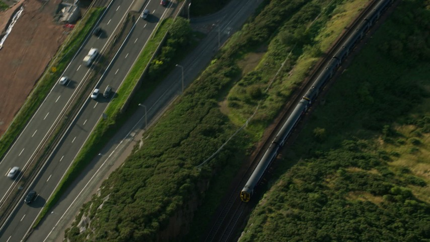 6K stock footage aerial video of tracking a commuter train beside a highway, North Queensferry, Scotland Aerial Stock Footage | AX111_067