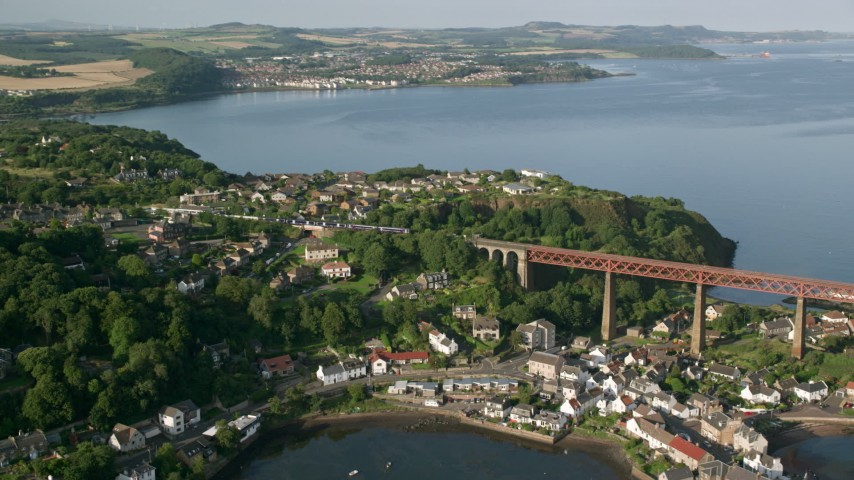 6K stock footage aerial video of a commuter train approaching the Forth Bridge, North Queensferry,  Scotland Aerial Stock Footage | AX111_071