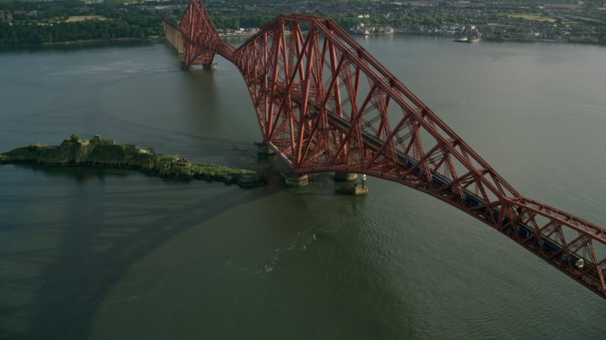 6K stock footage aerial video of tracking a commuter train on Forth Bridge spanning Firth of Forth, Scotland Aerial Stock Footage | AX111_077