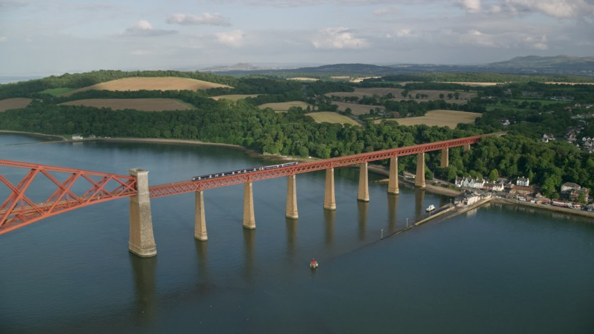 6K stock footage aerial video of a view of a commuter train on Forth Bridge over Firth of Forth in Scotland Aerial Stock Footage | AX111_081