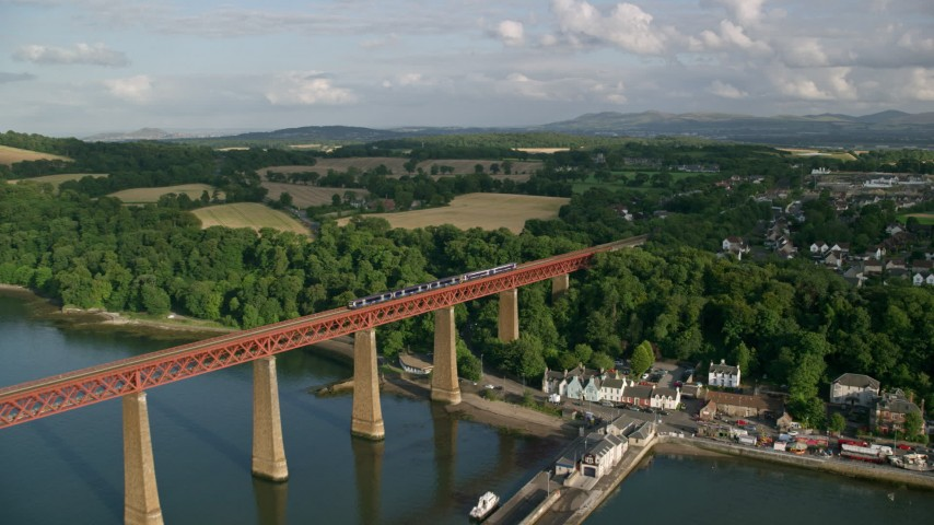6K stock footage aerial video of approaching a commuter train on Forth Bridge in Scotland Aerial Stock Footage | AX111_082