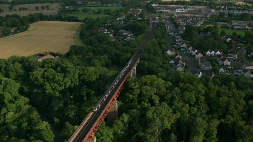 6K stock footage aerial video of flying over a commuter train moving between trees on Forth Bridge, Scotland Aerial Stock Footage | AX111_083