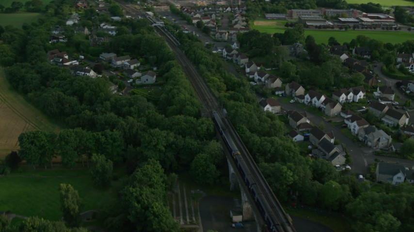 6K stock footage aerial video of a commuter train passing through a residential area, Edinburgh, Scotland Aerial Stock Footage | AX111_084
