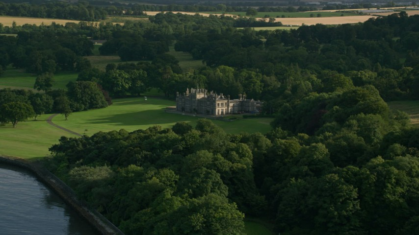 6K stock footage aerial video of Dalmeny House and trees in Edinburg,h Scotland Aerial Stock Footage | AX111_089