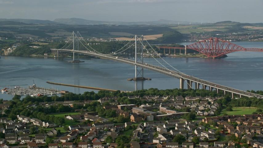 6K stock footage aerial video of Forth Road Bridge by residential neighborhood, Edinburgh, Scotland Aerial Stock Footage | AX111_100