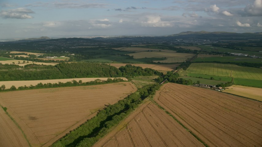 6K stock footage aerial video fly over rural landscape of farm fields and trees, Edinburgh, Scotland Aerial Stock Footage | AX111_103