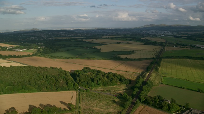 6K stock footage aerial video fly over rural landscape of farmland and trees, Edinburgh, Scotland Aerial Stock Footage AX111_104 | Axiom Images