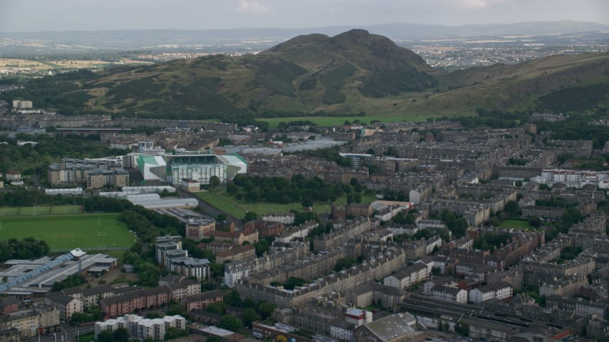 6K stock footage aerial video of the Easter Road soccer stadium and Arthur's Seat mountain peak, Edinburgh, Scotland Aerial Stock Footage | AX111_125