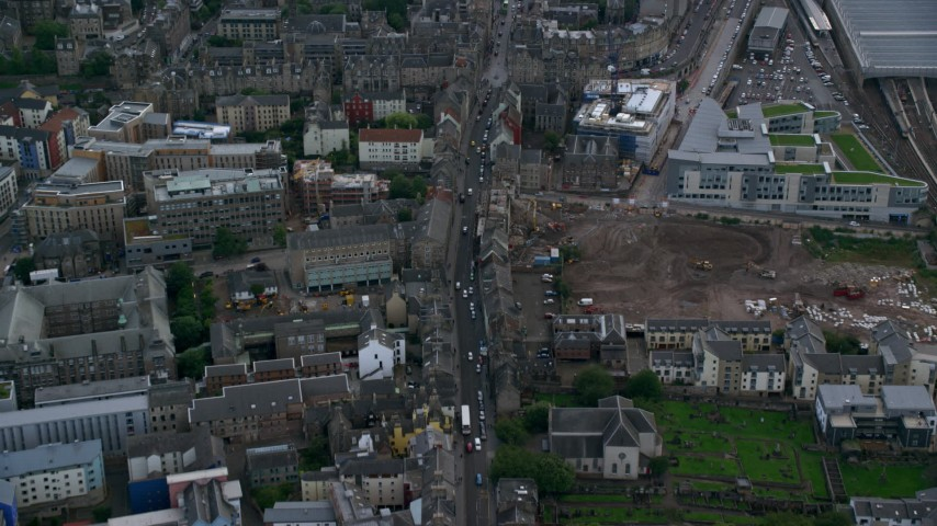 6K stock footage aerial video of following the city street through Canongate in Edinburgh, Scotland Aerial Stock Footage | AX111_131