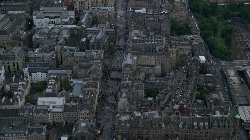 6K stock footage aerial video fly over Canongate crowds, to reveal cathedral in Edinburgh, Scotland Aerial Stock Footage AX111_133 | Axiom Images