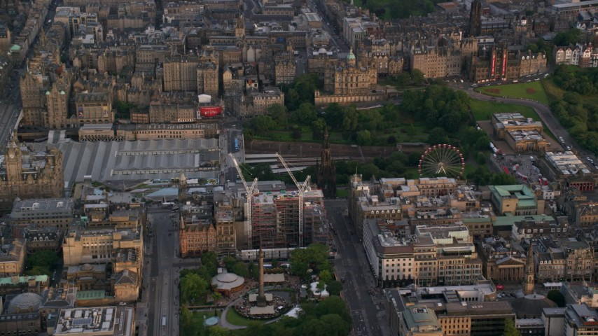 6K stock footage aerial video of Scott Monument, St Andrew Square, and train station, Edinburgh, Scotland at sunset Aerial Stock Footage | AX112_013