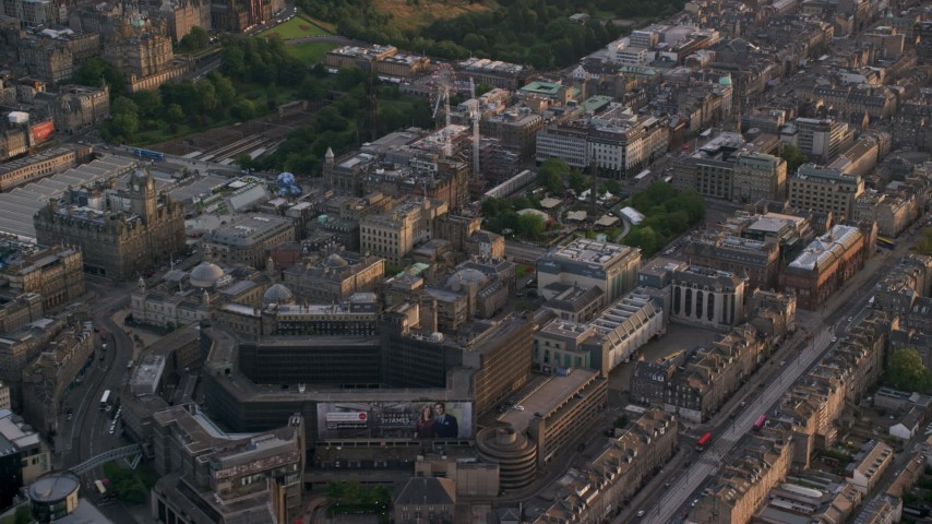 6K stock footage aerial video of St Andrew Square and shopping mall, Edinburgh, Scotland at sunset Aerial Stock Footage | AX112_015