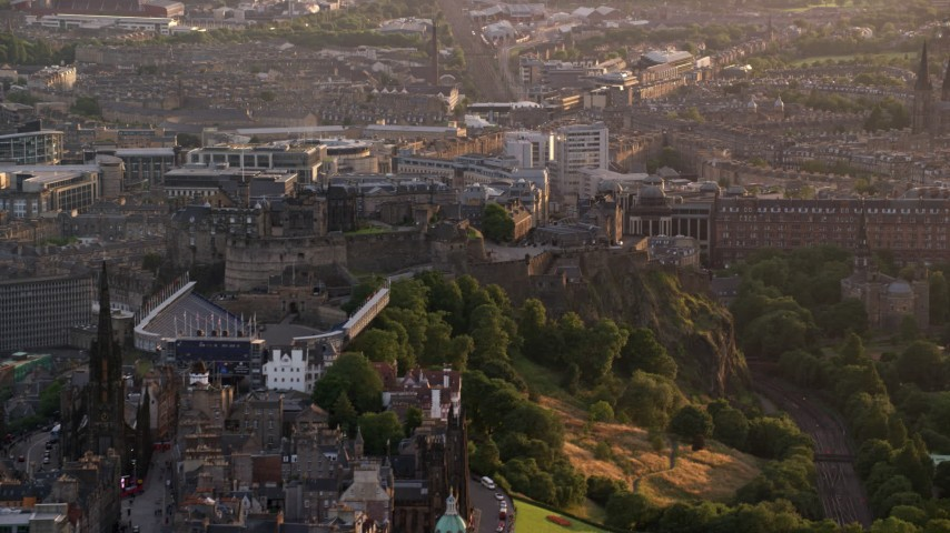 6K stock footage aerial video of flying by Edinburgh Castle, Scotland at sunset Aerial Stock Footage | AX112_020