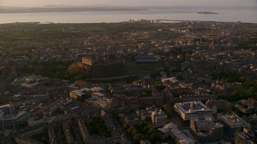 6K stock footage aerial video of flying by iconic Edinburgh Castle and cityscape, Scotland at sunset Aerial Stock Footage | AX112_050