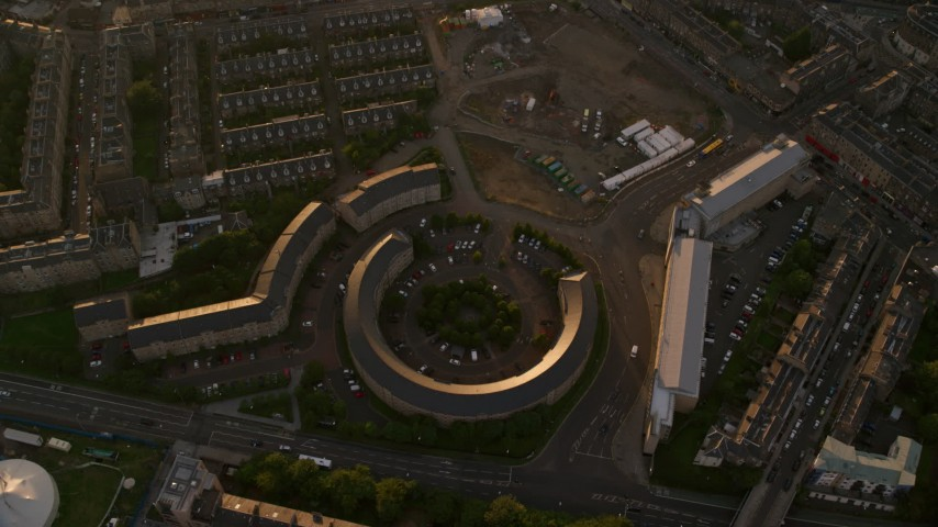 6K stock footage aerial video of tilting to a bird's eye view of office buildings at sunset in Edinburgh, Scotland Aerial Stock Footage | AX112_052