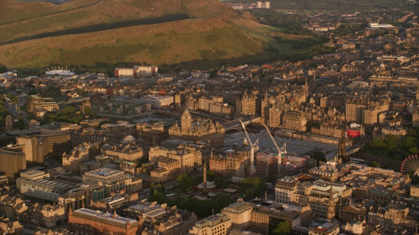 6K stock footage aerial video of Balmoral Hotel and cityscape of Edinburgh, Scotland at sunset Aerial Stock Footage | AX112_056