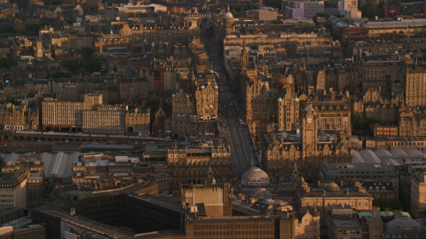 6K stock footage aerial video of flying by Balmoral Hotel and North Bridge, Edinburgh, Scotland at sunset Aerial Stock Footage | AX112_058