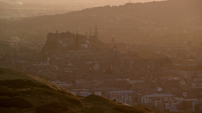 6K stock footage aerial video of a hazy view of historic Edinburgh Castle, Scotland at sunset Aerial Stock Footage | AX112_066
