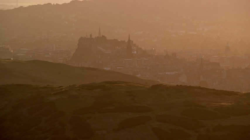 6K stock footage aerial video of Edinburgh Castle, Scotland during a hazy sunset Aerial Stock Footage | AX112_067
