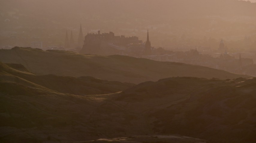 6K stock footage aerial video of iconic Edinburgh Castle and Arthur's Seat, Scotland during hazy sunset Aerial Stock Footage | AX112_068