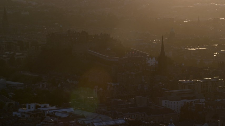 6K stock footage aerial video slowly flyby Edinburgh Castle and The Hub cathedral, Scotland at sunset Aerial Stock Footage | AX112_074