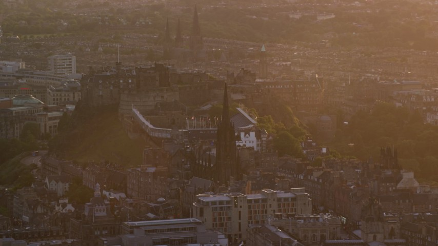 6K stock footage aerial video of slowly pass famous Edinburgh Castle and The Hub cathedral, Scotland at sunset Aerial Stock Footage | AX112_075