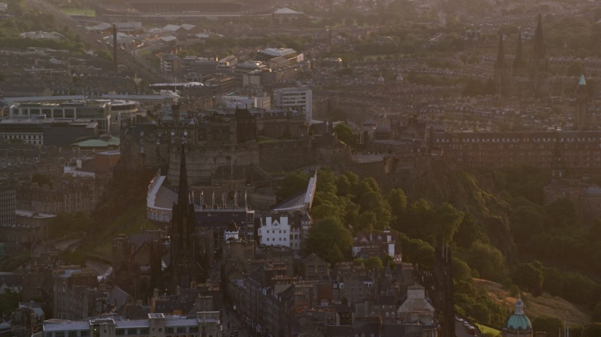 6K stock footage aerial video of passing iconic Edinburgh Castle and The Hub cathedral, Scotland at sunset Aerial Stock Footage   AX112_076