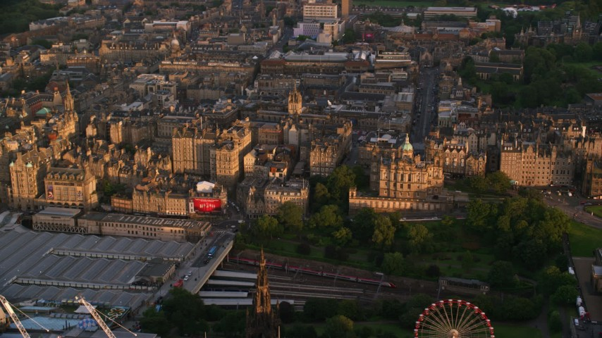 6K stock footage aerial video reverse view of Lloyds Bank Headquarters, reveal Scott Monument and train station, Edinburgh, Scotland at sunset Aerial Stock Footage | AX112_079