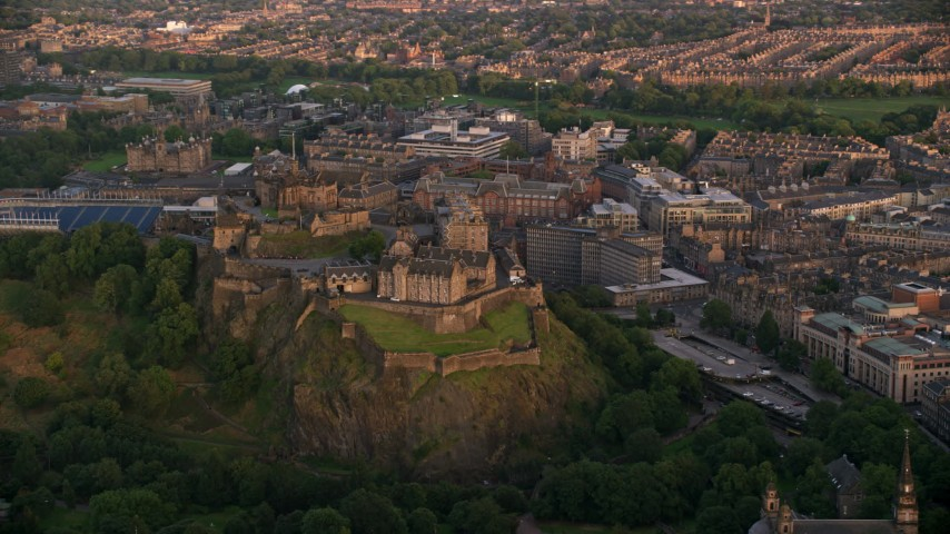 6K stock footage aerial video of a view of the famous hilltop Edinburgh Castle, Scotland at sunset Aerial Stock Footage | AX112_080
