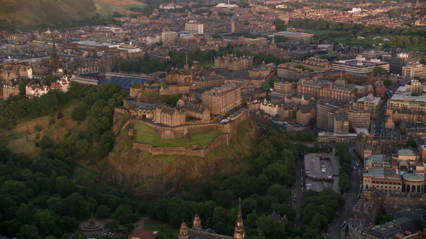 6K stock footage aerial video of Edinburgh Castle on a hill with a view of cityscape, Scotland at sunset Aerial Stock Footage | AX112_081