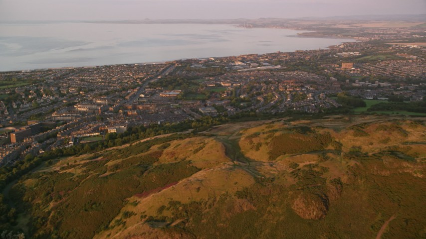 6K stock footage aerial video approach residential neighborhoods from Arthur's Seat, Edinburgh, Scotland at sunset Aerial Stock Footage | AX112_088