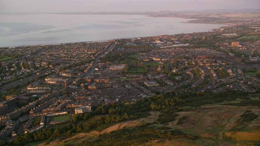 6K stock footage aerial video approach residential neighborhoods from Arthur's Seat, Edinburgh Scotland at sunset Aerial Stock Footage | AX112_089