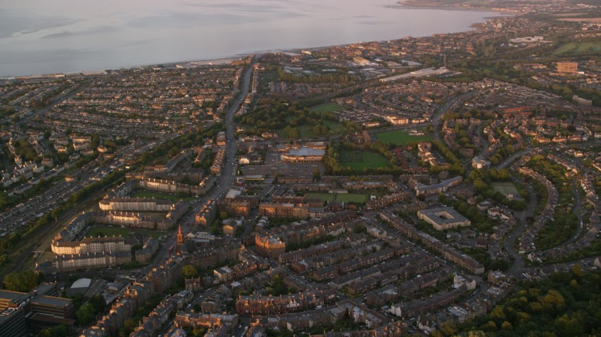 6K stock footage aerial video of residential neighborhoods near the water, Edinburgh, Scotland at sunset Aerial Stock Footage | AX112_090