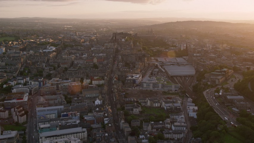 6K stock footage aerial video of following Canongate toward Edinburgh Castle, Scotland at sunset Aerial Stock Footage | AX112_093