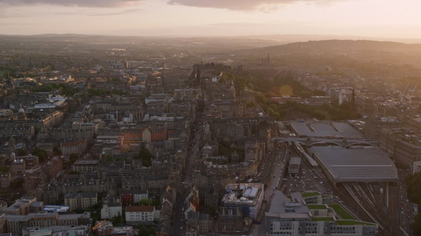 6K stock footage aerial video of flying over Canongate toward Edinburgh Castle, Scotland at sunset Aerial Stock Footage | AX112_094