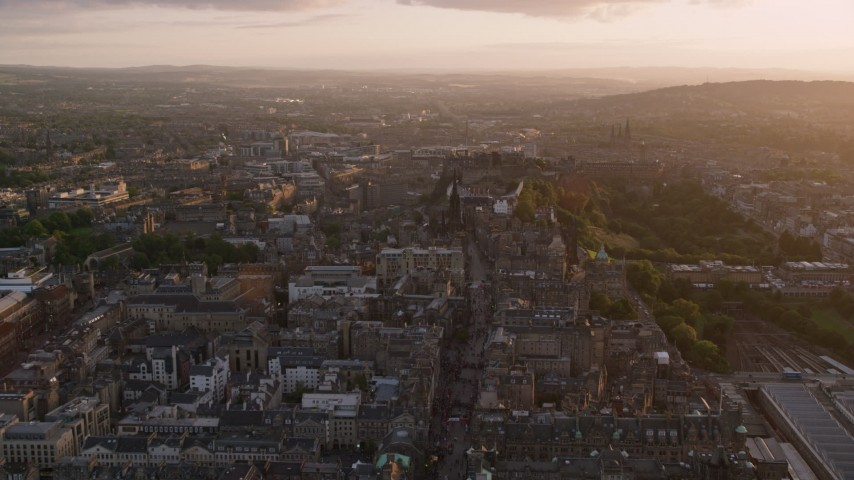 6K stock footage aerial video fly over Canongate to approach historic Edinburgh Castle, Scotland at sunset Aerial Stock Footage AX112_095 | Axiom Images