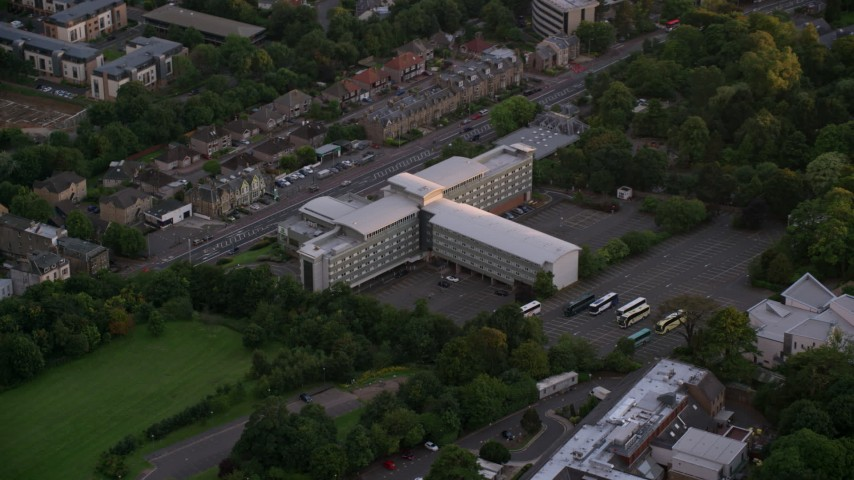6K stock footage aerial video of flying by a t-shaped office building in Edinburgh, Scotland at sunset Aerial Stock Footage | AX112_112
